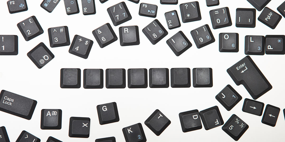 Loose scattered alphanumeric keys from a computer keyboard, with a line of blank keys representing tax code