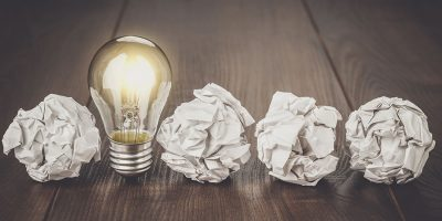 Lit lightbulb in a row of crumpled balls of paper representing ideas for innovation that are eligible for R&D tax credit.