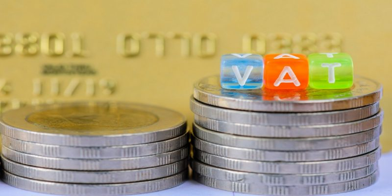 Photo of VAT (Value Added Tax) letter cubes on stacks of coins with gold credit card background