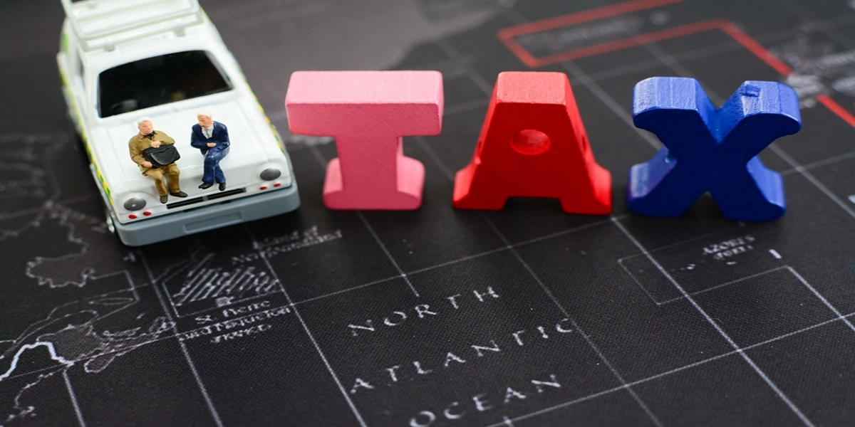Miniature people sitting on a toy car next to the word tax