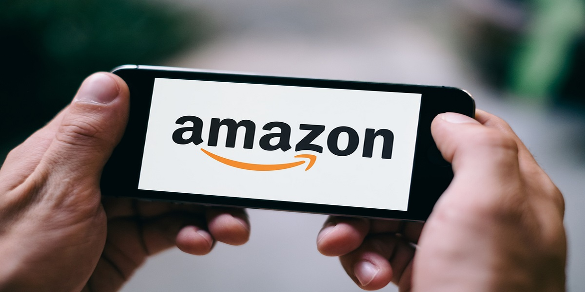amazon tax represented by amazon app open on a smartphone, held horizontally by two man's hands in a photo