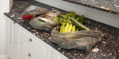 Back from shopping with purchases in three single use carrier bags, placed on marble worktop in kitchen.