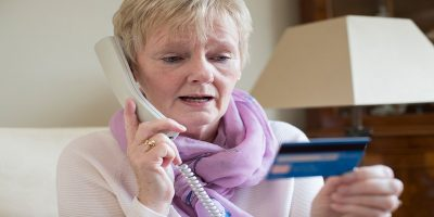 confusing tax system helping fraudsters. Shown by photo of a confused woman on the phone giving her bank card details.
