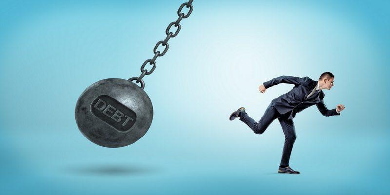 hmrc asset seizure shown by businessman running from wrecking ball with debt written on it.