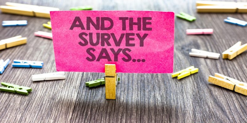 Photo of pink post it held by a peg saying 'and the survey says'. Showing idea of survey highlighting generations divide concerning how we spend out taxes.