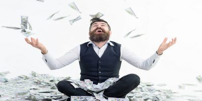 Wealthy man sitting in a pile of cash throwing money around. Illustrating that high earners pay high tax bills.