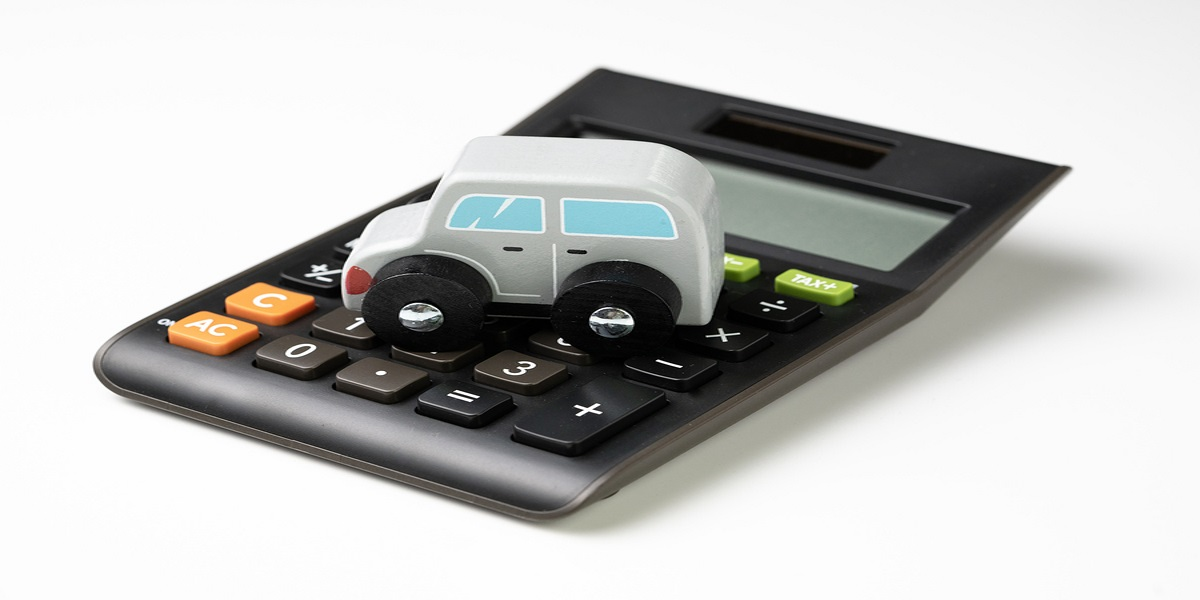 Workplace parking levy shown by photo of a grey to car parked on top of a black calculator, on a white background.