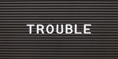 Black felt board background, word 'trouble' in white capital letters at the forefront.