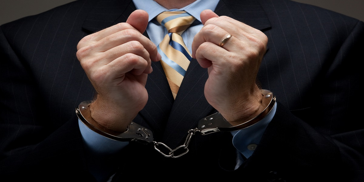 Photo of suited man in handcuffs to show potential of HMRC's new corporate tax evasion rules.