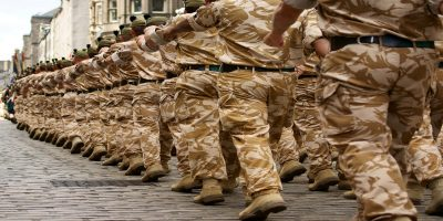 Photo taken from behind a troop of marching British soldiers in camouflage uniforms.