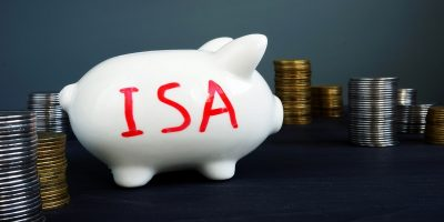 Red capital letters spelling ISA written on a white piggy bank, surrounded by stacks of silver and copper coins.