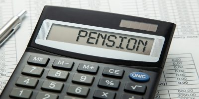 Black calculator sitting on top of financial paperwork. Word PENSION written on calculator's screen. To show pension tax overpayment calculation problem.