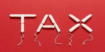 Photo of the word tax made out of tampons,on a red background.