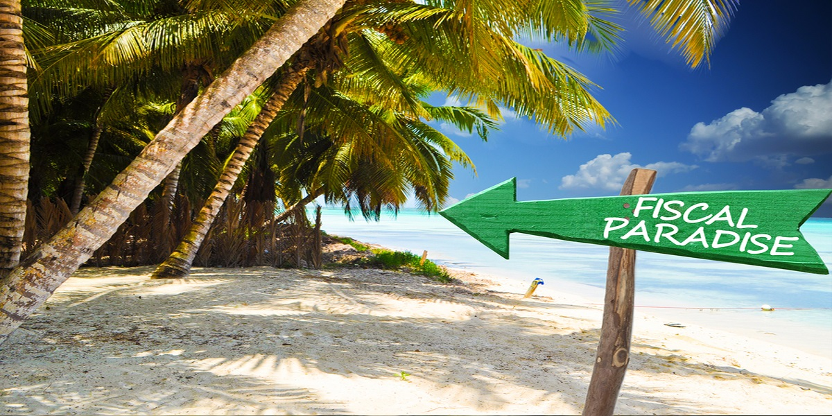 Photo of a tropical island, sandy beach with palm trees and a sign pointing to it that says Fiscal Paradise. The concept of a tax haven.