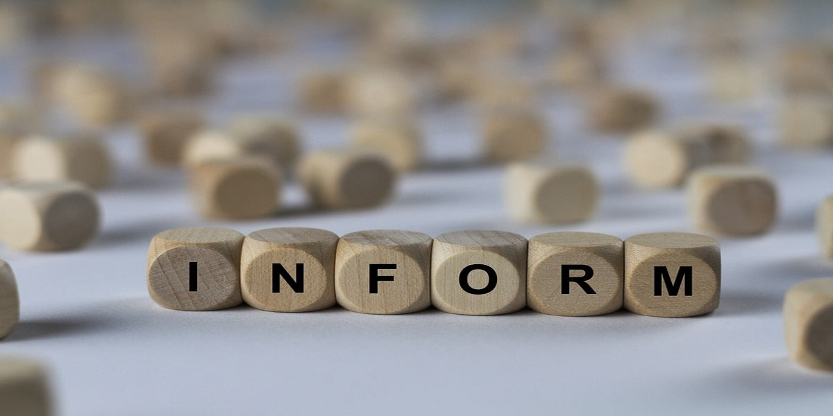 Wooden cubes with black capital letters printed on them on a table. In the foreground, in focus, spelling out the word informer. In the out of focus background, a scattering of cubes on the rest of the table.