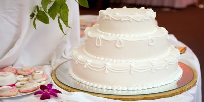 Three tier white wedding cake with pretty white piping decoration. Sitting on a decorated table beside a plate of wedding themed biscuits.