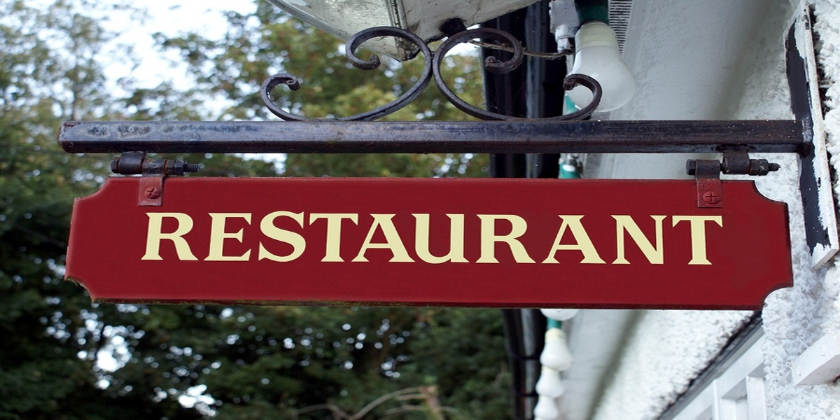 Restaurant sign, white lettering on a deep red background, handing form a metal strut attached to the wall.