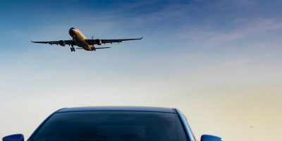 Plane landing from a clear blue sky. Top of a car in the foreground. Illustrate Scotland's travel taxes to protect the environment.