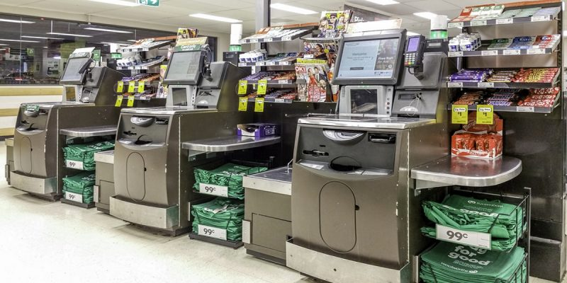 Photo of three self service checkouts in an Australian Woolworths. Illustrating the proposed new 1p tax on self service checkout use to fund intergenerational development projects.