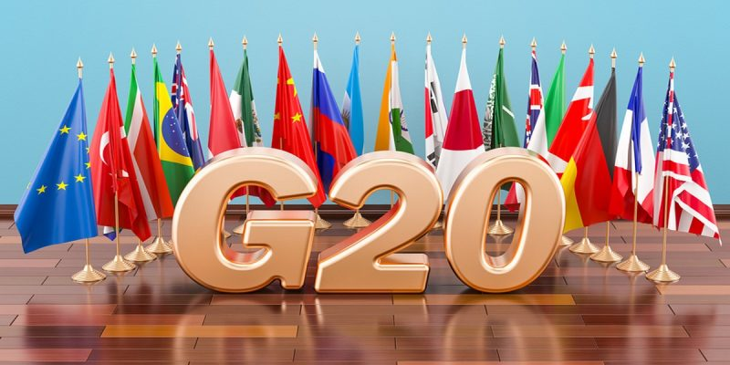 Rose gold G20 figures sitting in the centre of an arc of flags representing all 19 G20 countries, on a wooden table.