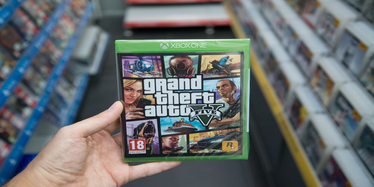 Photo of a hand holding the game Grand Theft Auto V, in a shop. Illustrating the story about UK Corporation Tax avoidance and huge Video Games Tax Relief claims.