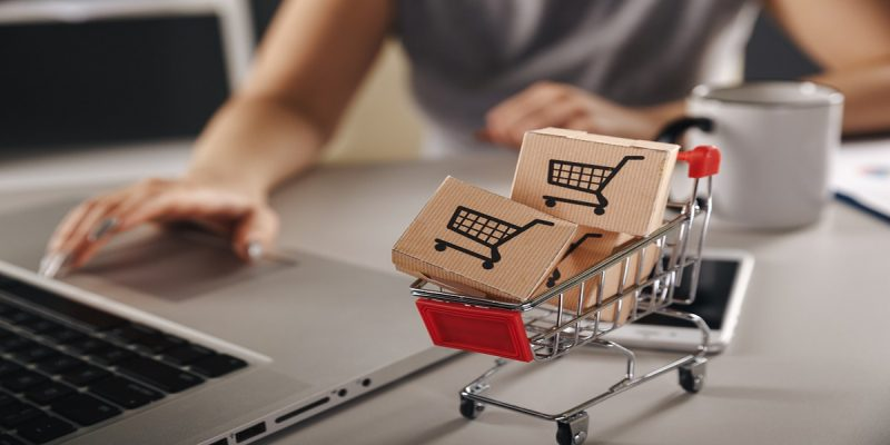 Foreground focus on a miniature shopping trolley containing mini boxes with common shopping cart icon on them. Representing ecommerce. Blurred background of a woman's hand over silver laptops' mouse, presumably ordering these items. Also mobile phone and mug on the desk.