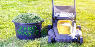 On grass, lawnmower on the right, bucket of newly mown clippings in a bucket labelled 'Zero Waste' on the left.