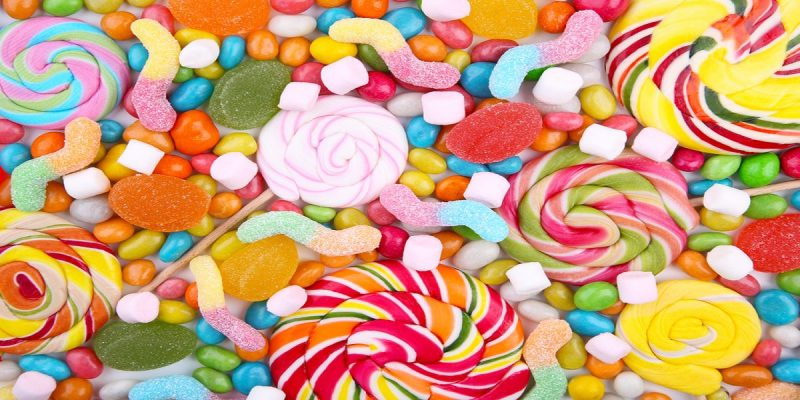 Pile of assorted colourful sweets, including mini marshmallows, fizzy snakes, jellies and round spiraled lollipops.