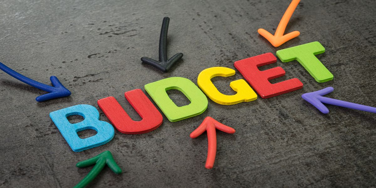 Multicoloured arrows pointing to the word budget, in multicoloured block capitals, in the middle of a blackboard.