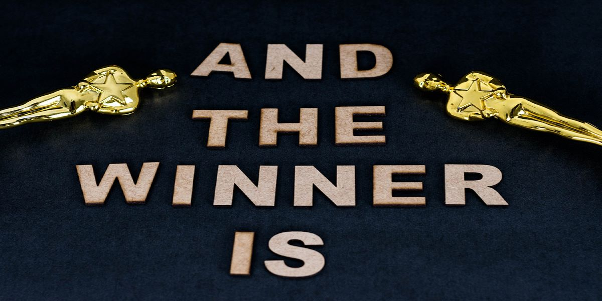 Black background, 'And the winner is' written in gold block capital letters in the centre. One Oscars statue diagonally facing inwards on either side.