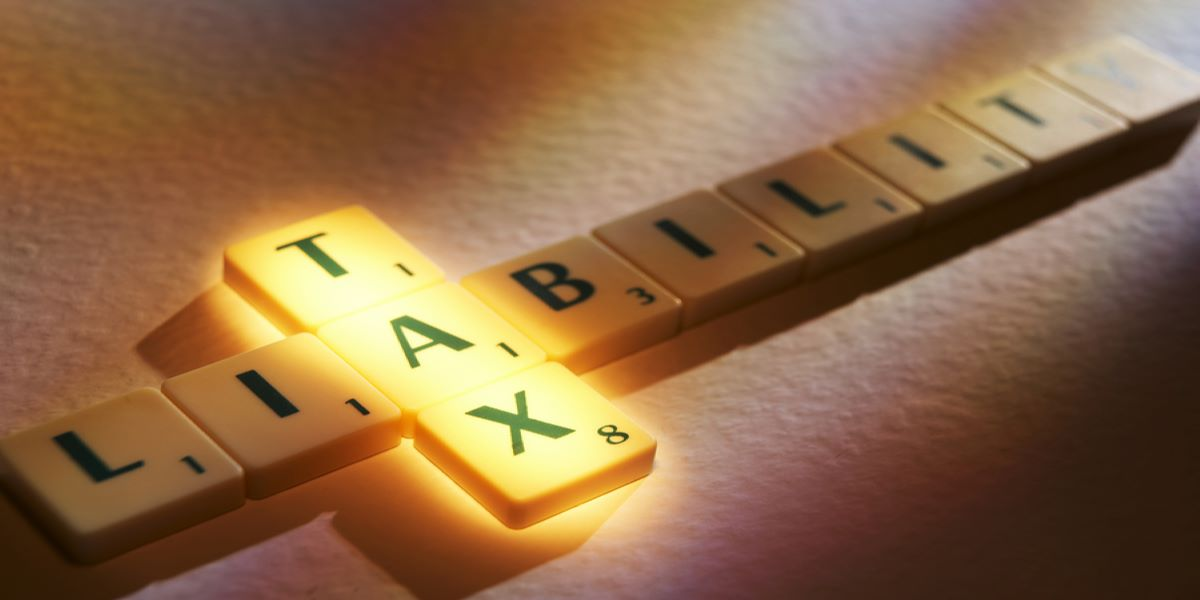 Scrabble tiles spelling TAX LIABILITY, intersecting at the A. TAX illuminated..