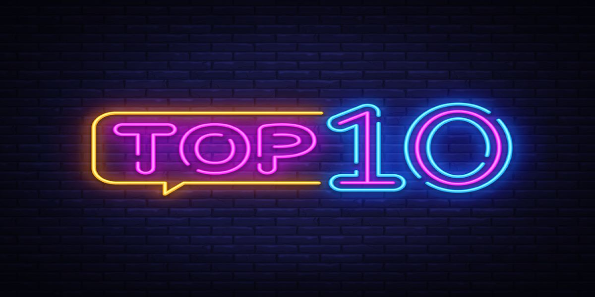 Purple, yellow and blue neon sign saying Top 10, brick wall background.
