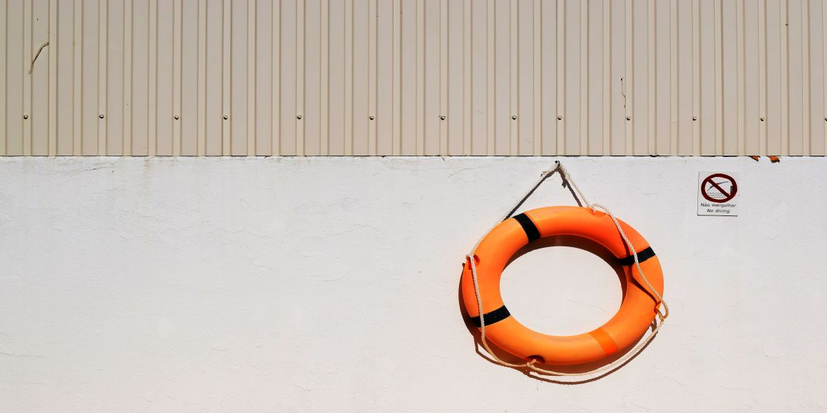 Circular orange life buoy handing on a hook on a white external wall.