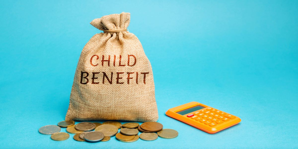 Hessian sack labelled CHILD BENEFIT. Variety of coins in front of the sack. Bright yellow calculator to the right. All on a light blue background.