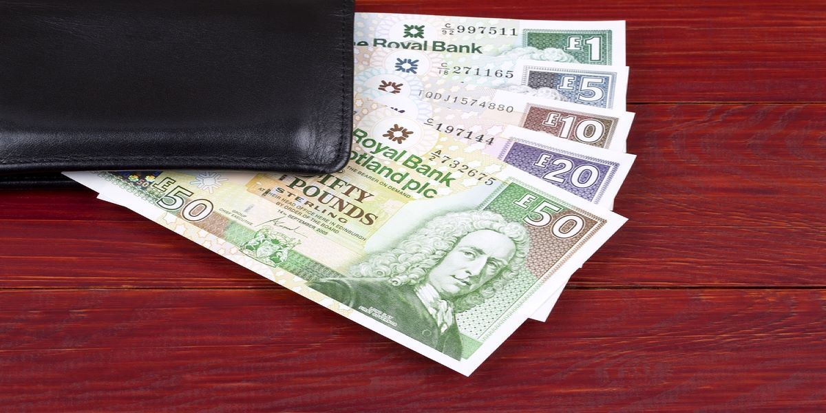 Range of Scottish notes fanned out on a wooden table, weighted down by the corner of a black leather wallet.