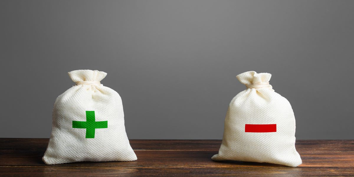 Two white money bags sitting on a table. The one on the right with a green positive cross. On the right, a red negative minus symbol. Showing the budget deficit situation because of the corona virus pandemic.