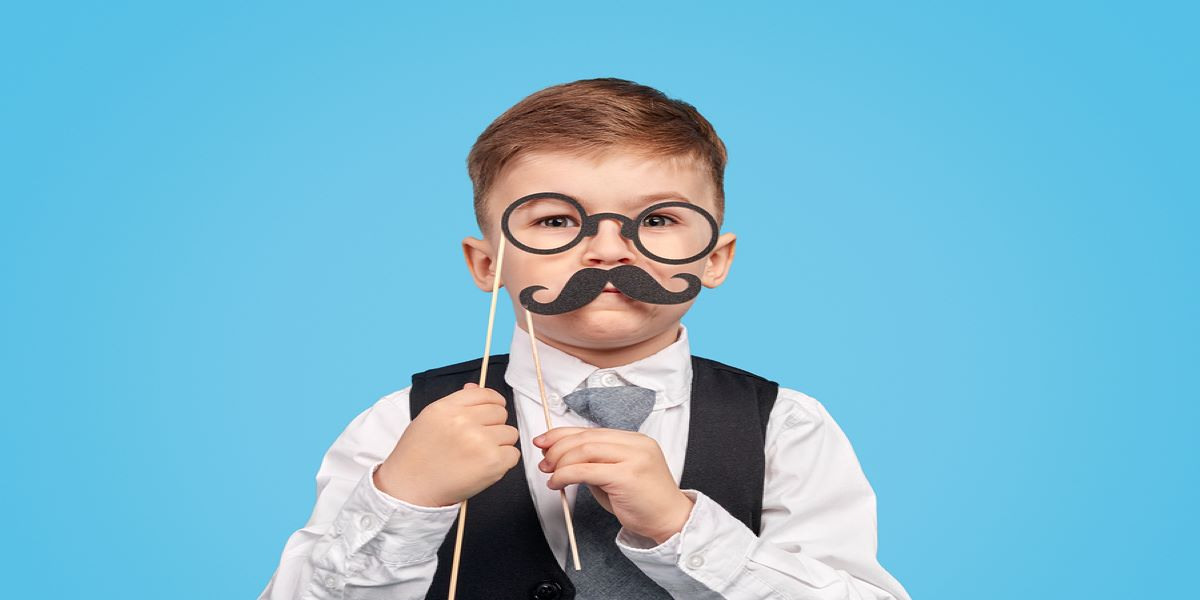 Little boy dressed in shirt, tie and waistcoat,wearing glassed and holding a fake moustache. Illustrating the idea of fake furlough scheme claims.