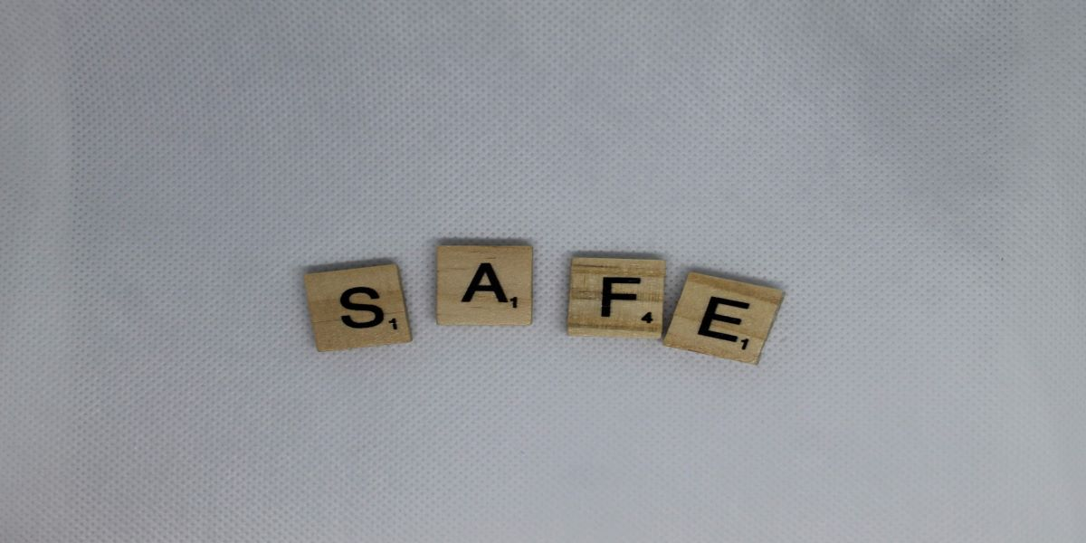Scrabble tiles spelling the word safe, on a white fabric background.