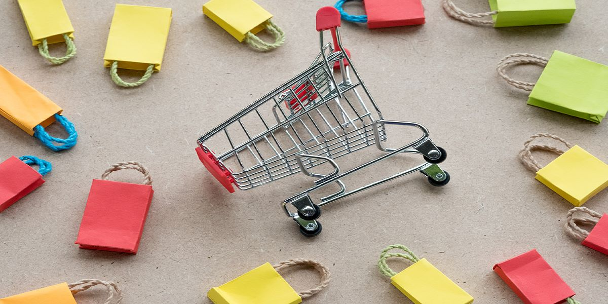 Photo of one mini shopping trolley lying on its side, surrounded by mini colourful cardboard shopping bags with string handles.,