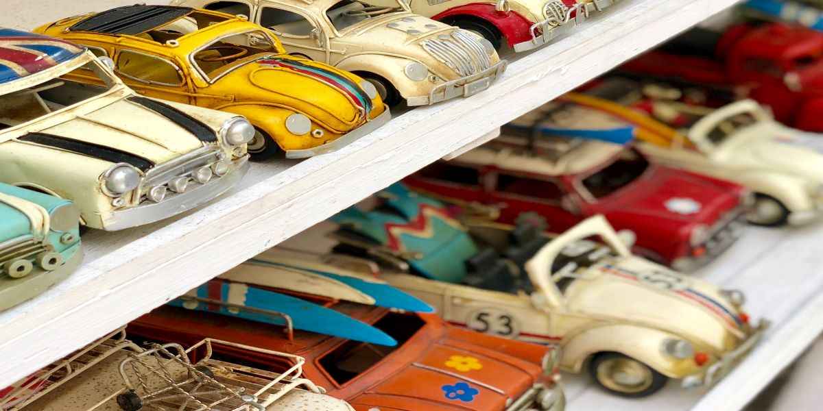 Two shelves of vintage toy cars.