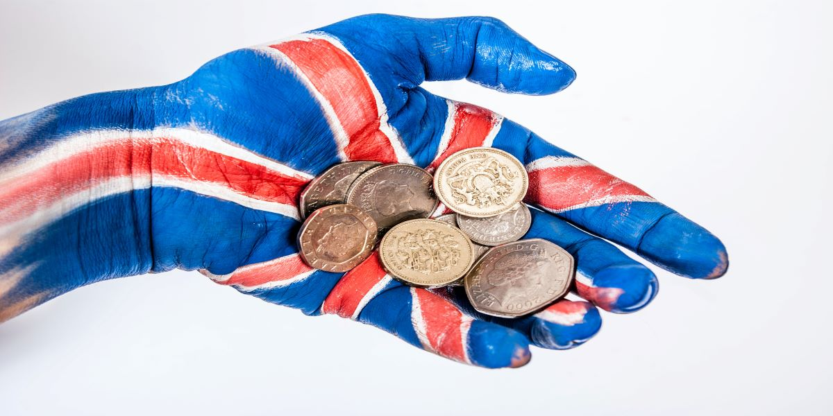 Left hand body painted in a UK flag, holding a variety of British coins.