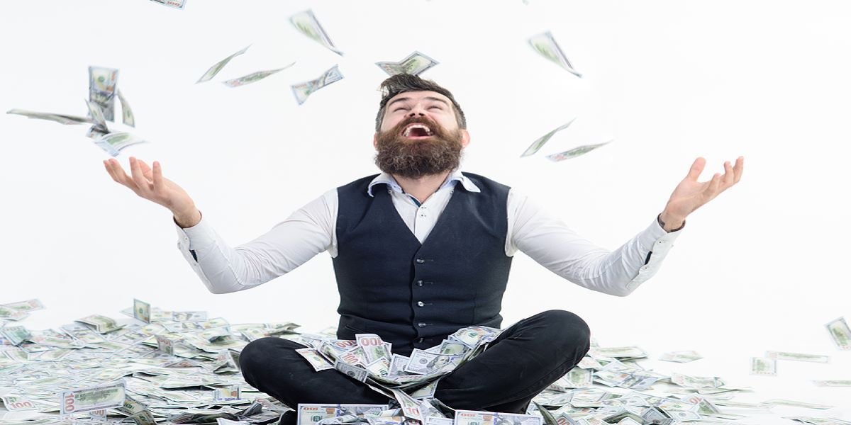 White bearded man in a business suit, sits cross-legged in a pile of paper money. Happily throwing it in the air.