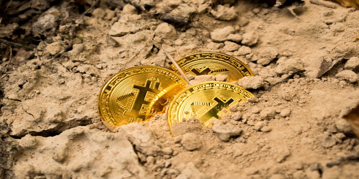 3 gold Bitcoin coins partially buried in the sand.