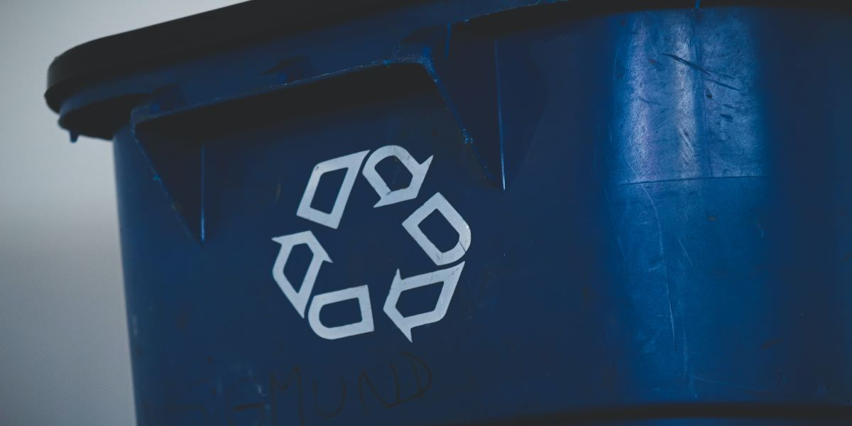 Photo of a blue wheelie bin with the recycling icon, in white.