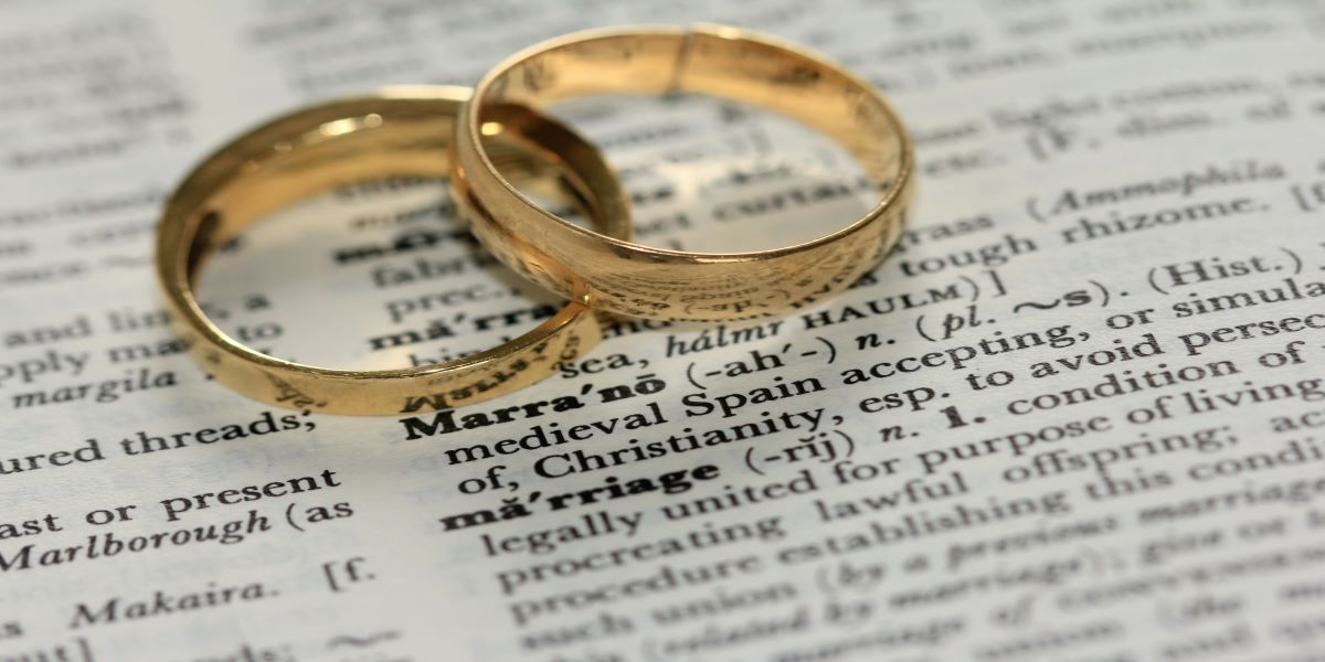 Two gold band wedding rings, sitting on top of a dictionary open at the word marriage.