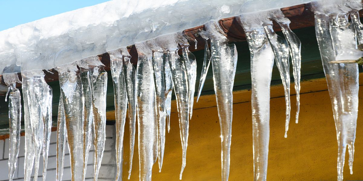 Photograph of icicles handing from a snow covered roof.