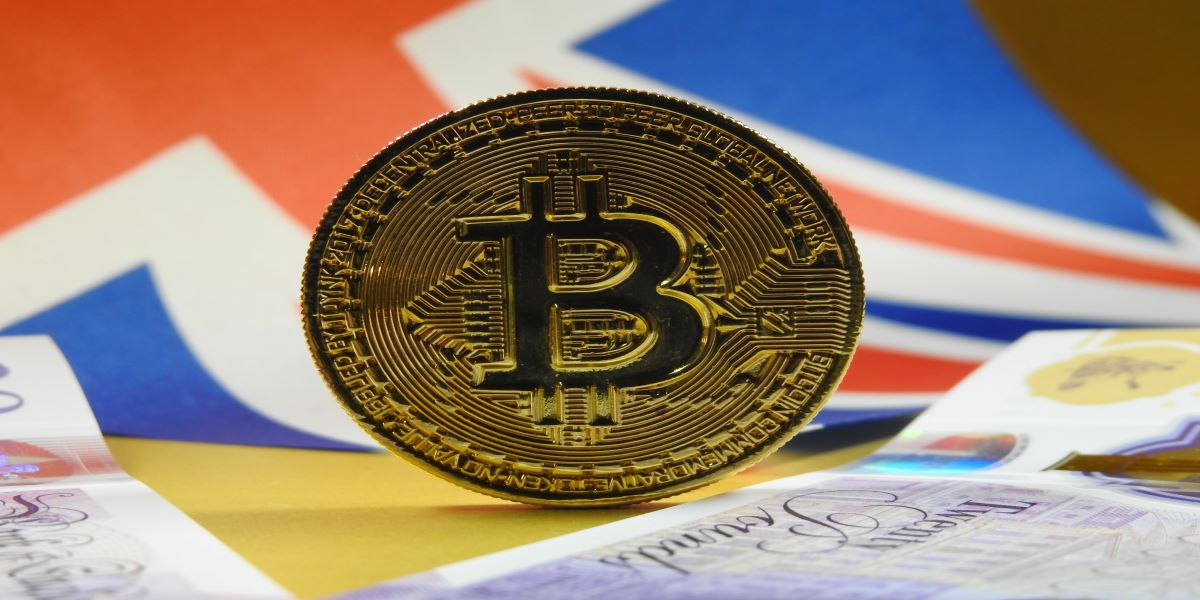 Photo of a gold Bitcoin coin standing on its edge on a table with £20 notes and a Union Jack in the background.