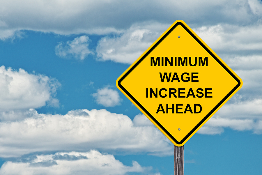 Created image of a roadside saying Minimum Wage Increase Ahead, background of a cloudy blue sky.