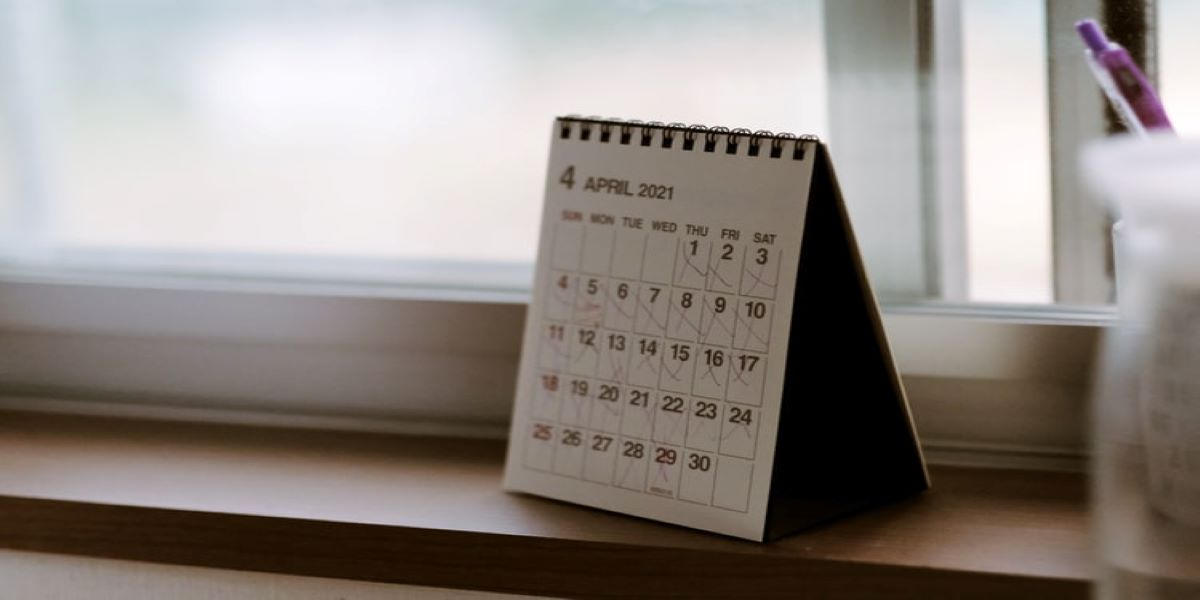 Photo of an A5 calendar, open to April, standing on a window sill.