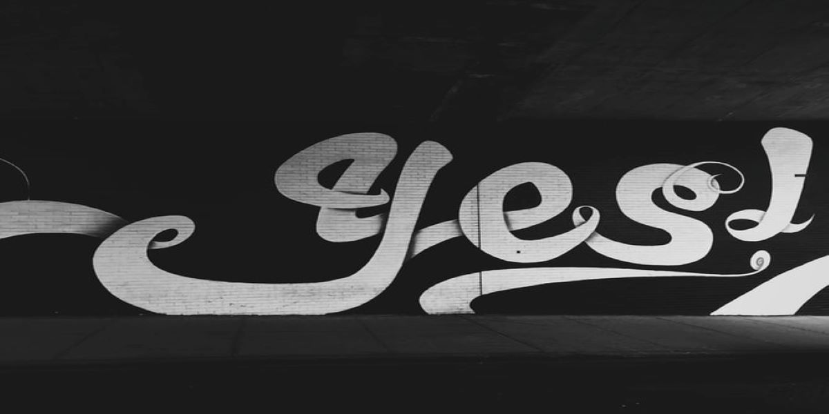 Street sign of the word 'Yes!' painted in white on a black background.